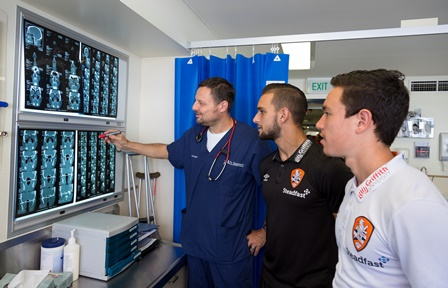 St Andrew's emergency doctor Peter Forgiarini with Roar players Jack Hingert (in black) and Devante Clut (in white).